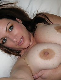 Busty girlfriend takes selfshot pictures of her huge natural tits laying in bed